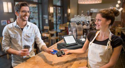 Mann zahlt mit seiner Kreditkarte kontaktlos in einem Café.