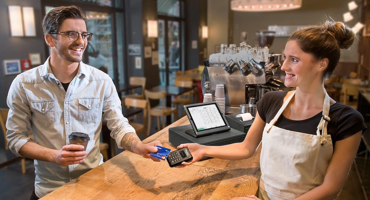 Mann zahlt mit seiner Kreditkarte kontaktlos in einem Café